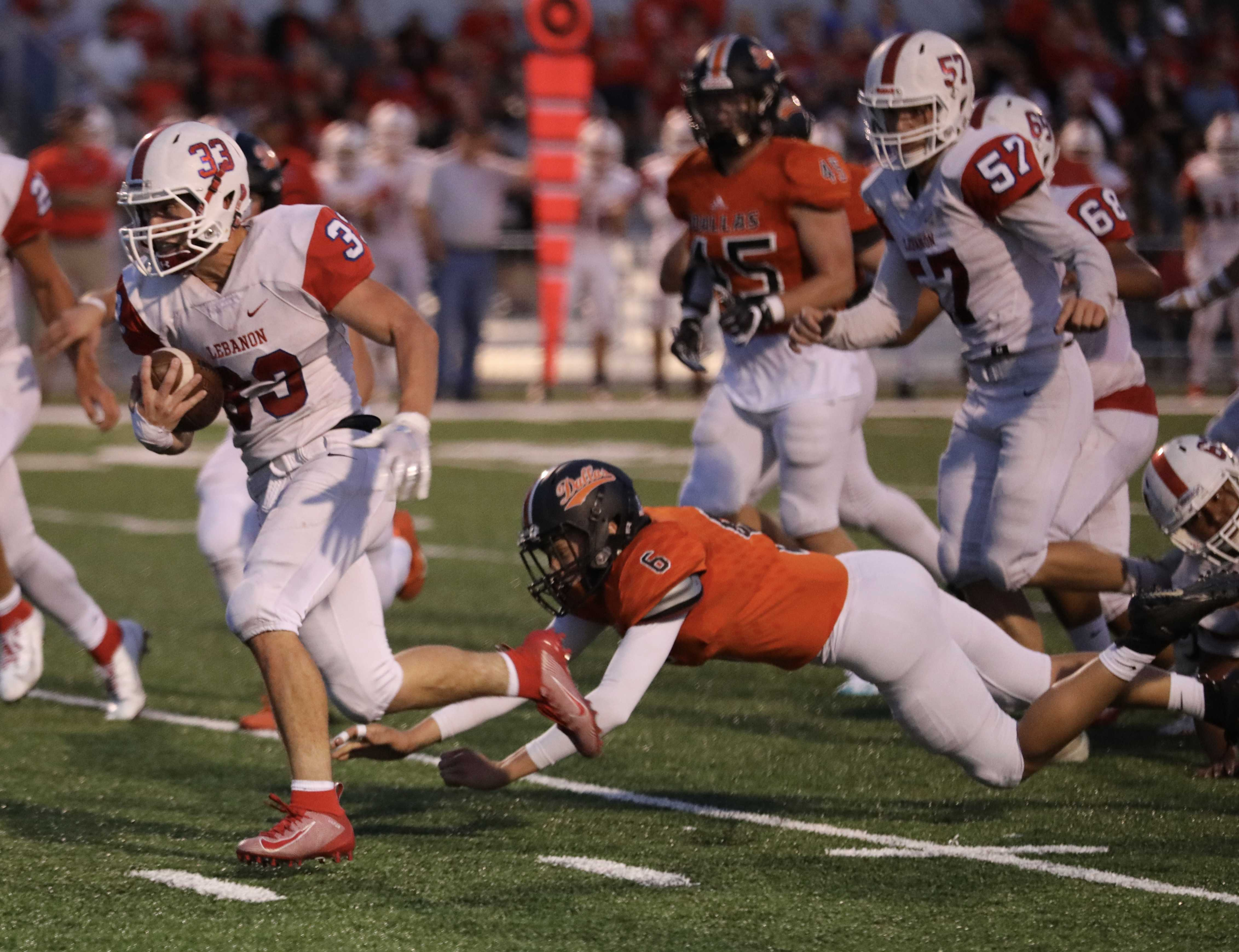 Lebanon running back Brock Barrett escapes the tackle of Dallas' Luke Hess for a 28-yard touchdown run. (Norm Maves Jr.)