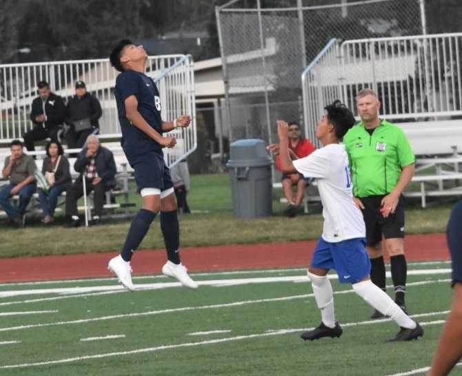 Stayton's Santos Navarro (left) goes after a header in Thursday's win over Woodburn. (Photo by Jeremy McDonald)