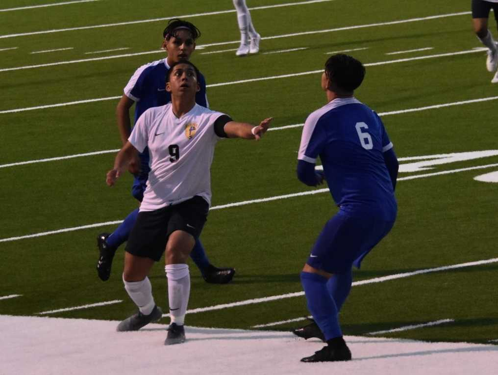 Stayton's David Ramirez (center) fights for possession against Woodburn. (Photo by Jeremy McDonald)