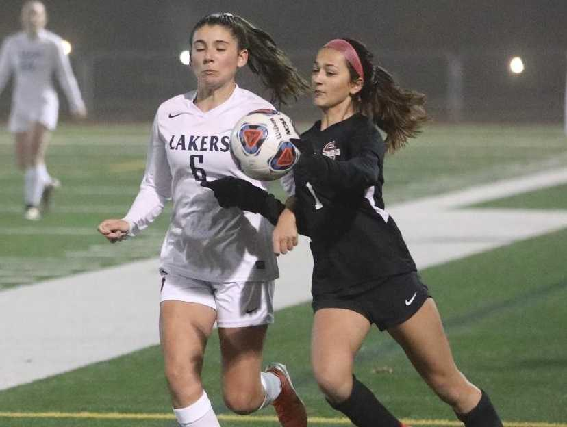 Lake Oswego's Natalie Redpath (6) and Sherwood's Alysia Alvarado contest a bouncing ball. (Photo by Norm Maves Jr.)