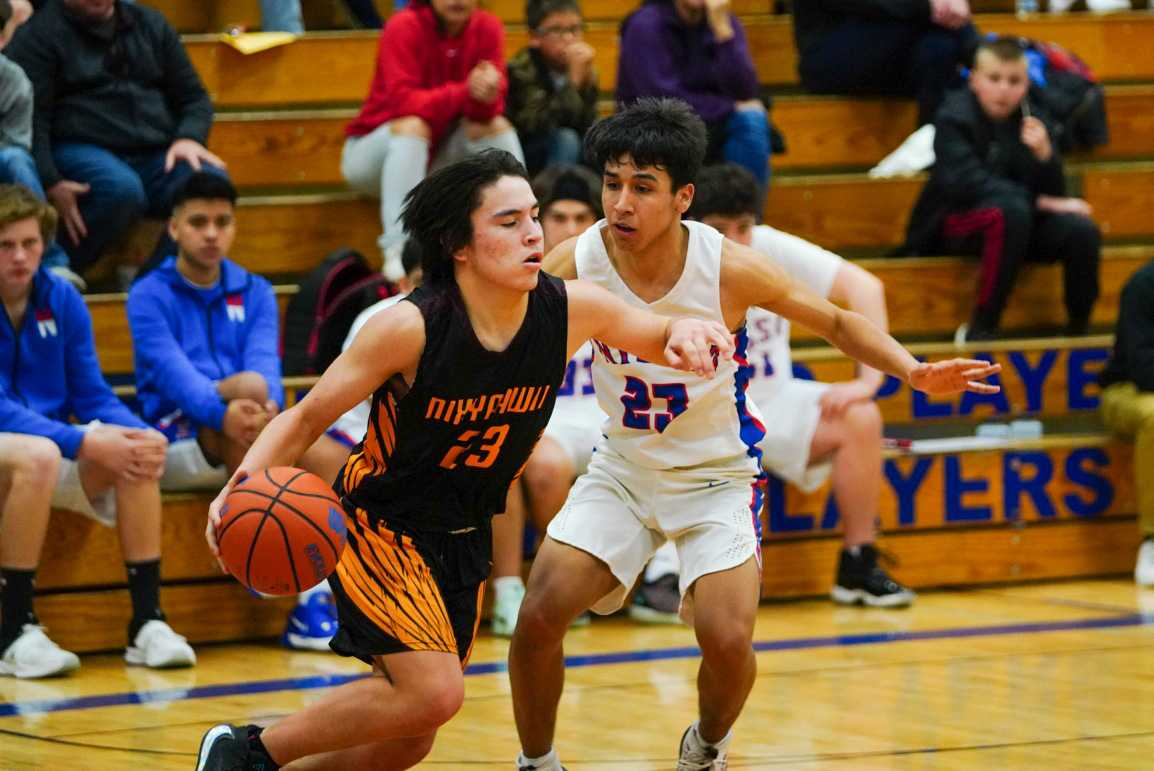 Nixyaawii's Tyasin Burns (23) drives against Nyssa's Pedro Chavez on Monday. (Randy Seals/Eastern Oregon Sports Photos)