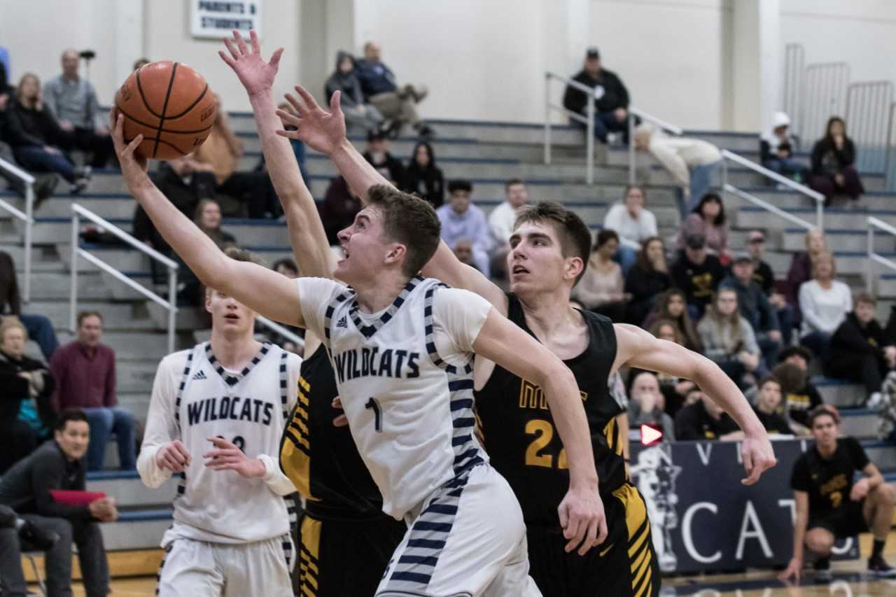 Wilsonville's Gabe Reichle (1) drives past Milwaukie's Mason Plumb (22) on Tuesday night. (Photo by Greg Artman)