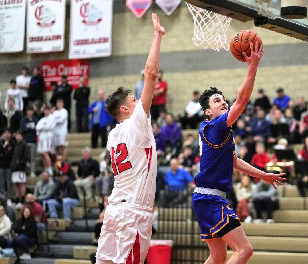 Barlow's Jesse White drives to the basket against Clackamas' Ben Gregg on Tuesday night. (Photo by Jon Olson)