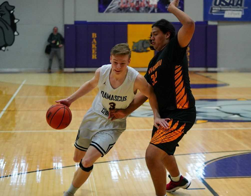 Damascus Christian's Spencer Powers drives against Nixyaawii's Magi Moses. (Randy Seals/Eastern Oregon Sports Photos)