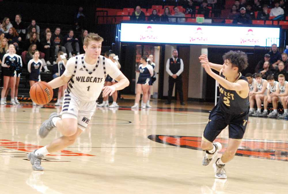Wilsonville point guard Gabe Reichle drives on West Albany's Koby Ruiz. Reichle had 11 first-half points in the Wildcat win
