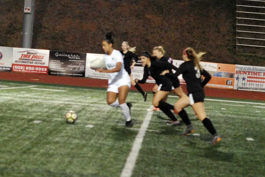 Gabi Brown (21) eludes a cadre of Tualatin defenders. Seconds later, she sent a screamer into the net for a 1-0 lead