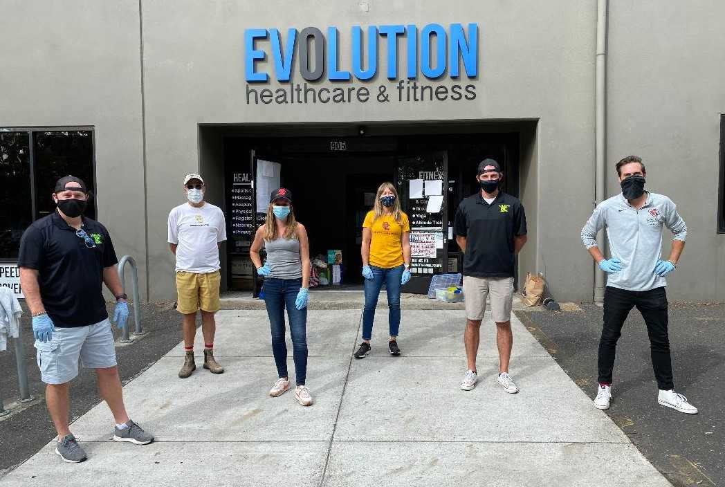 Coaches met to accept community donations at Evolution Fitness.
