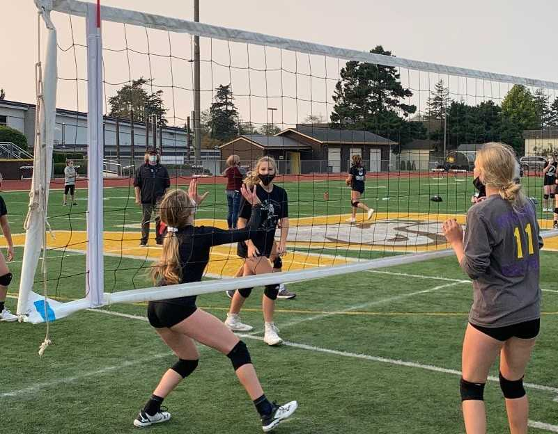 North Bend's Bridget Gould (left) sets to Sophia Macduff in an outdoor volleyball match Tuesday. (Photo courtesy North Bend HS)