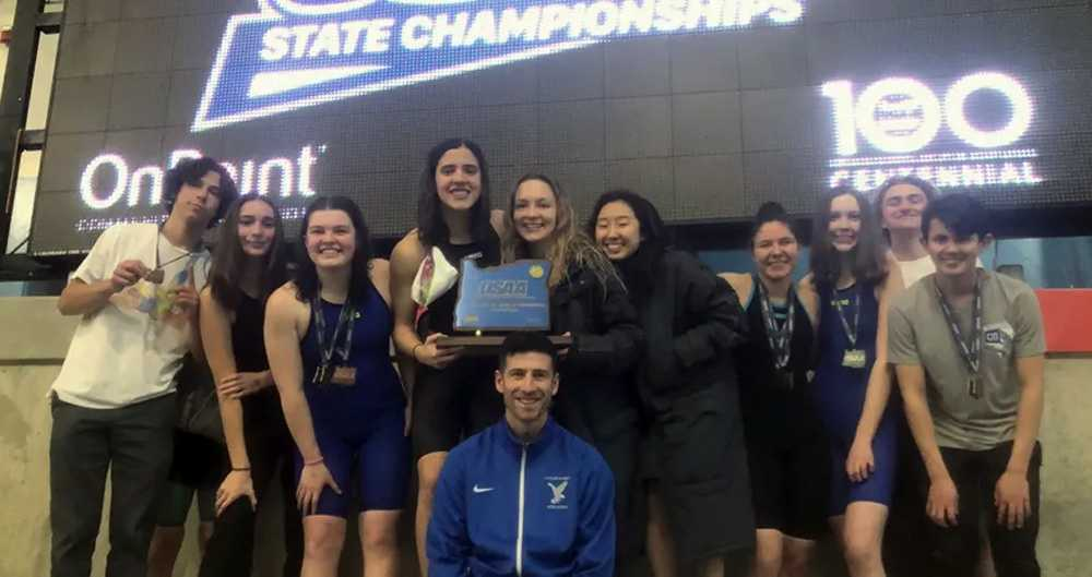 Swim team members from Catlin Gabel's most recent state championship pose with the coach and the blue trophy