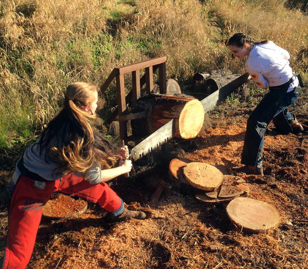 Two Clatskanie girls cut into a log. It was worth a buck.