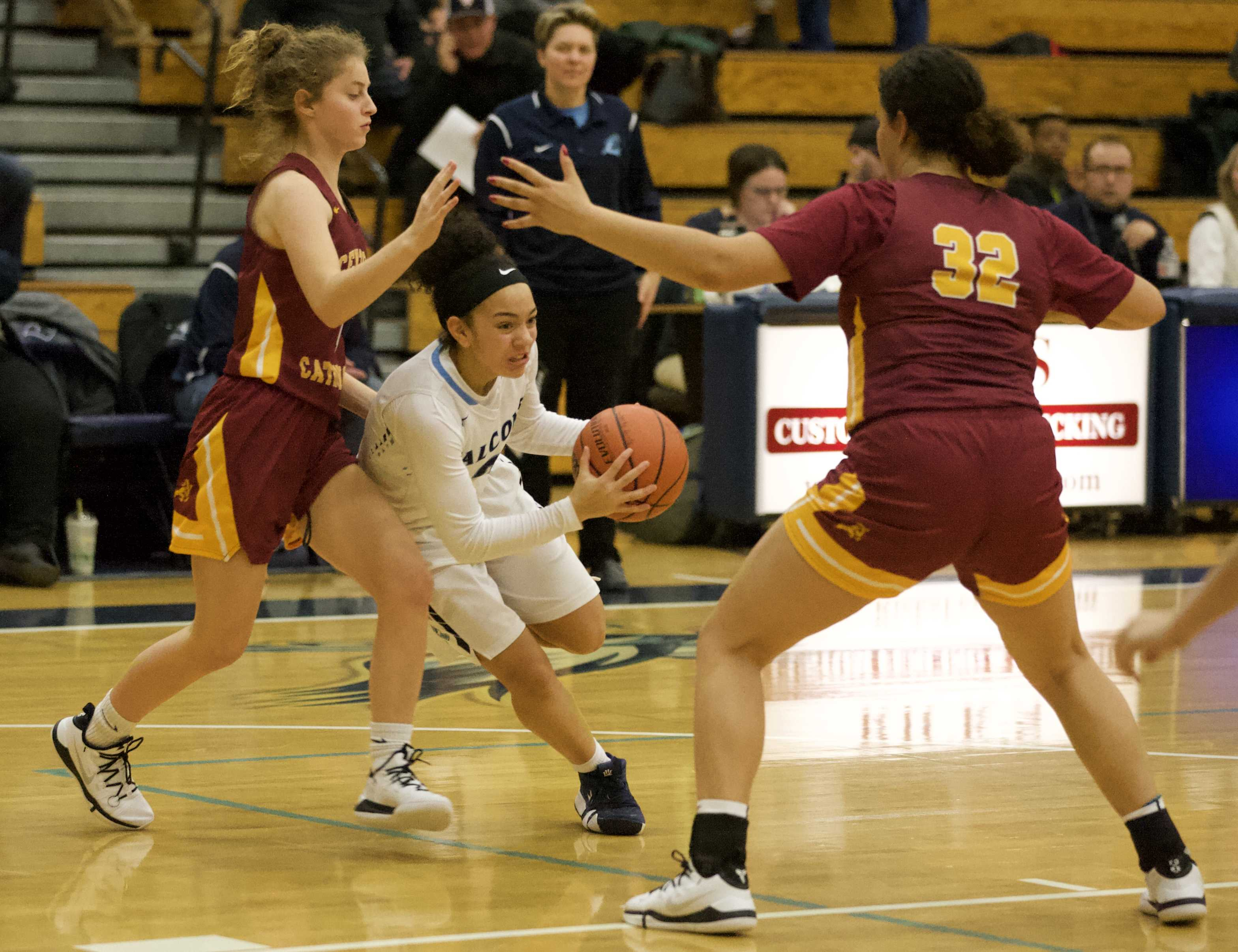Liberty's Taylin Smith slices between Maylani Montgomery, left, and Bella Scarlett of Central Catholic.